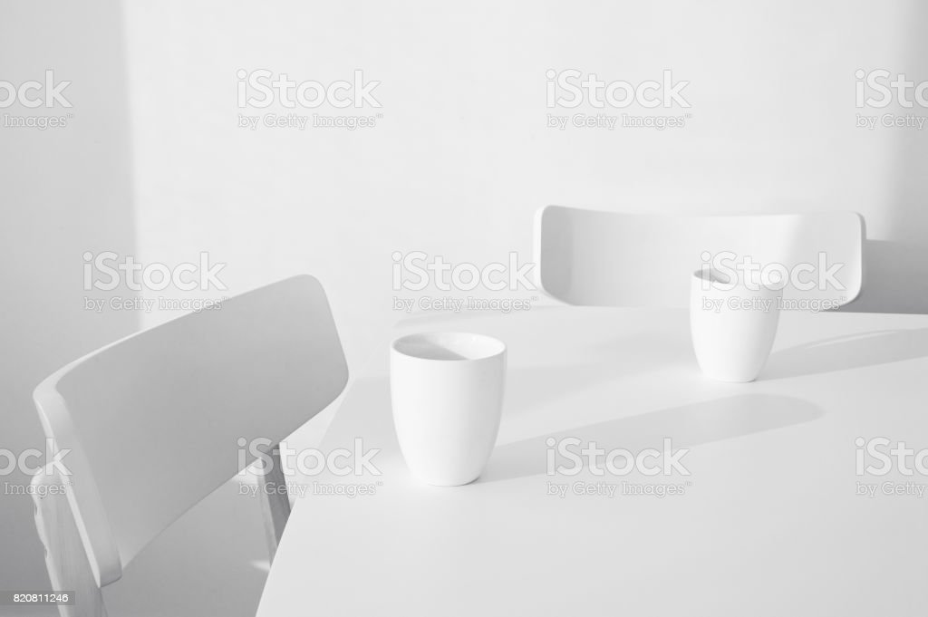 Two empty chairs with two mugs stock photo