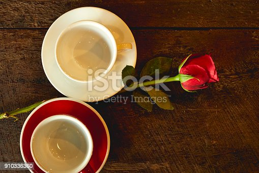Two empty cups with red roses placed on an old wooden top view.