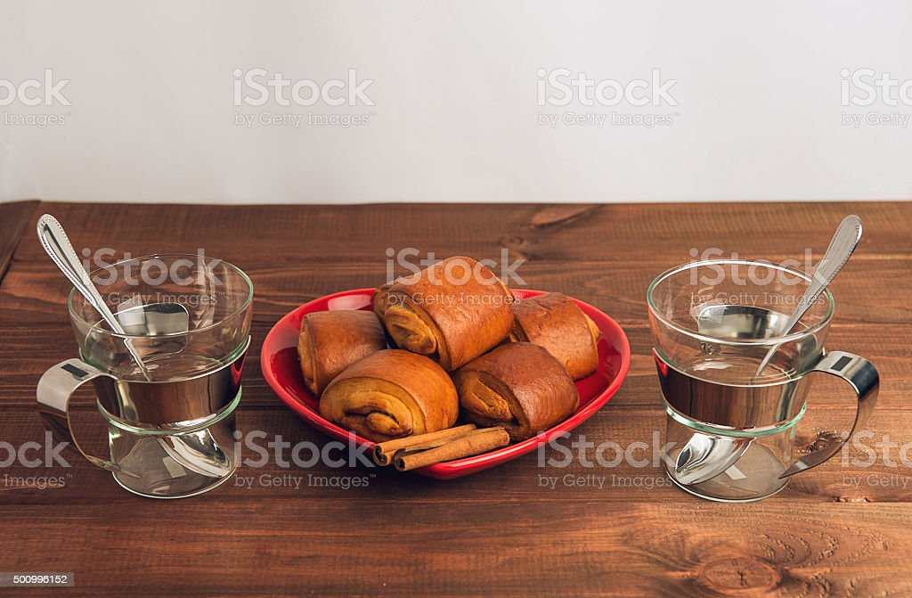 Two empty glass cups with metal handles and cinnamon rolls stock photo