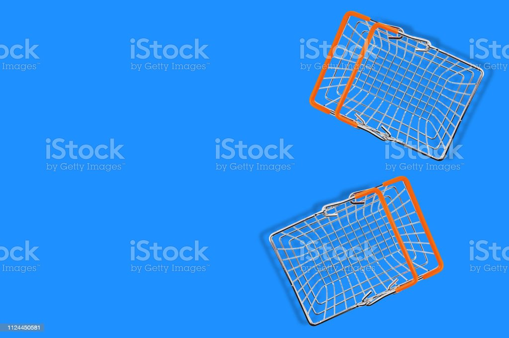 Two empty market baskets made from chrome metal wire and orange...