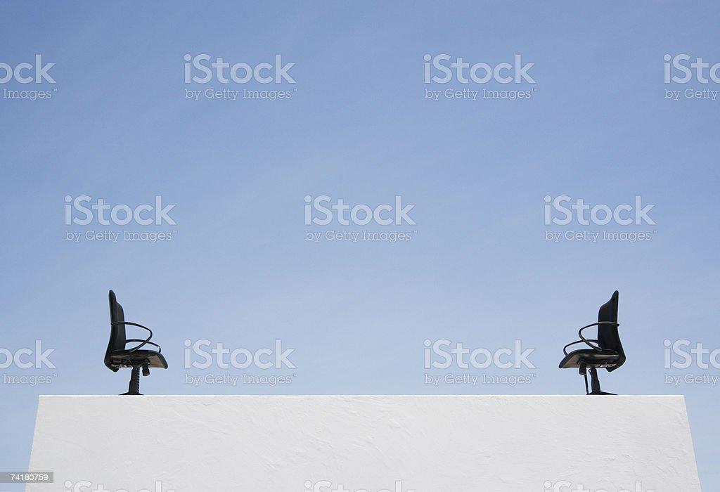 Duas cadeiras de escritório vazio na parede com céu azul foto de stock royalty-free