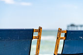 Two empty reclining beach chairs, wooden yellow recliners with blue fabric on beach with sky, ocean sea coast shore, fishing pier in blurred background in Okaloosa island, Florida Panhandle