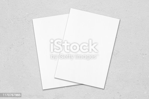 1171907064 istock photo Two empty white poster mockups lying diagonally on top of each other on grey concrete background 1170767965