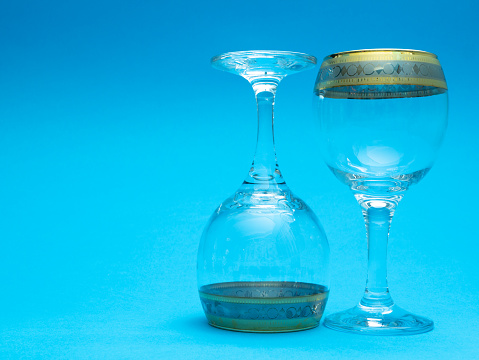 two empty wine glasses on blue background