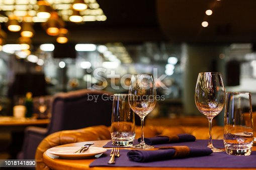 Two empty wine glasses sitting in a restaurant on a warm sunny afternoon.