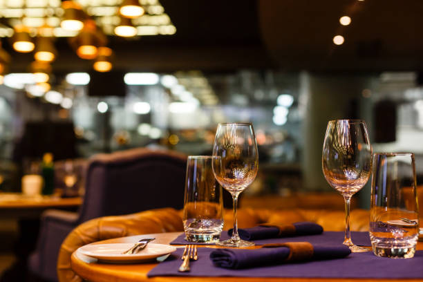 Two empty wine glasses sitting in a restaurant on a warm sunny afternoon. Two empty wine glasses sitting in a restaurant on a warm sunny afternoon. grace stock pictures, royalty-free photos & images