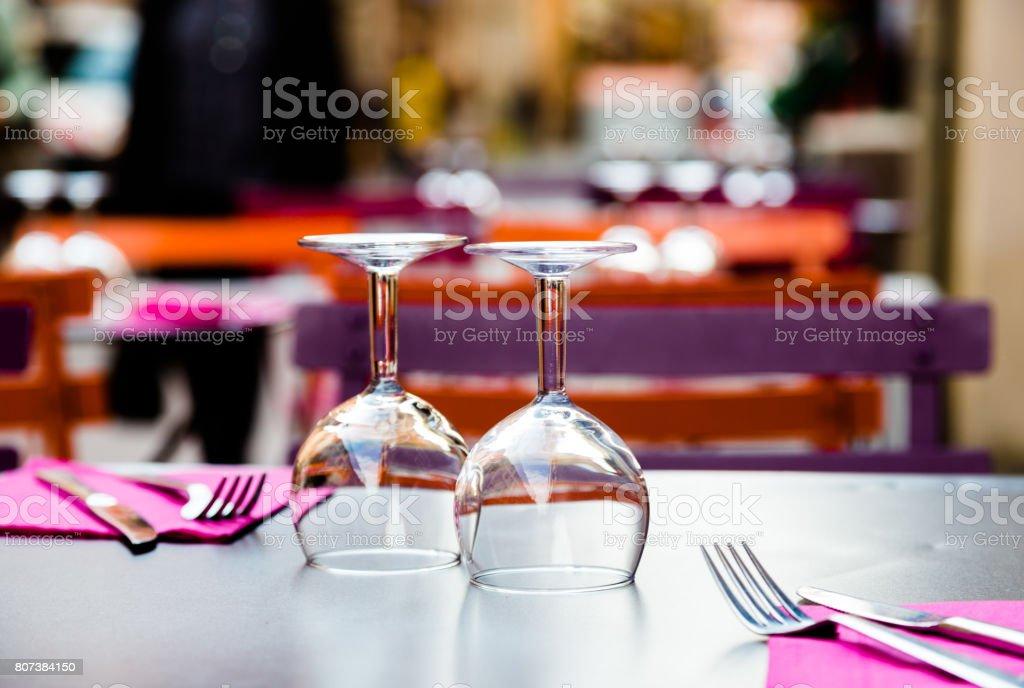 Dois copos de vinho vazia acima-lado-para baixo e talheres na mesa no restaurante - foto de acervo