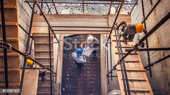 istock Two engeneers looking blueprint on a construction site 810297422