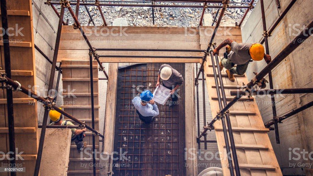 Zwei Ingenieuren suchen Blaupause auf einer Baustelle – Foto
