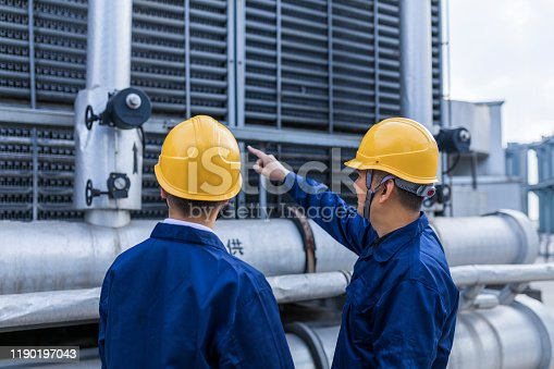 Two engineer colleagues examining to cooling tower equipment.