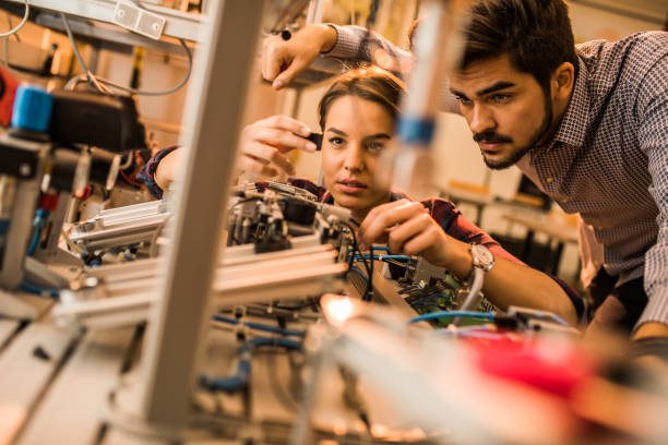 Two engineering students working on electrical component of a machine in laboratory. stock photo