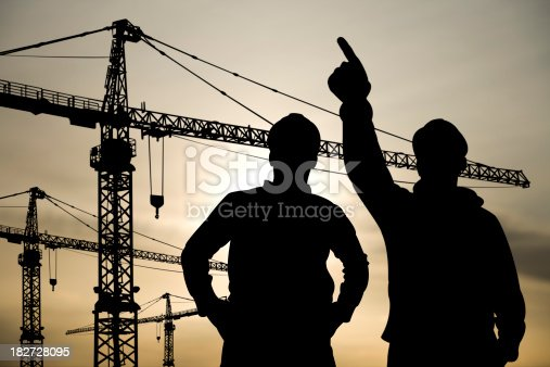 Royalty free image of two construction workers surveying a construction site.  Three cranes appear slightly out of focus behind them.