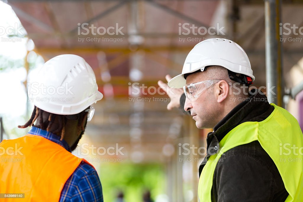 Two engineers at work among scaffolding stock photo
