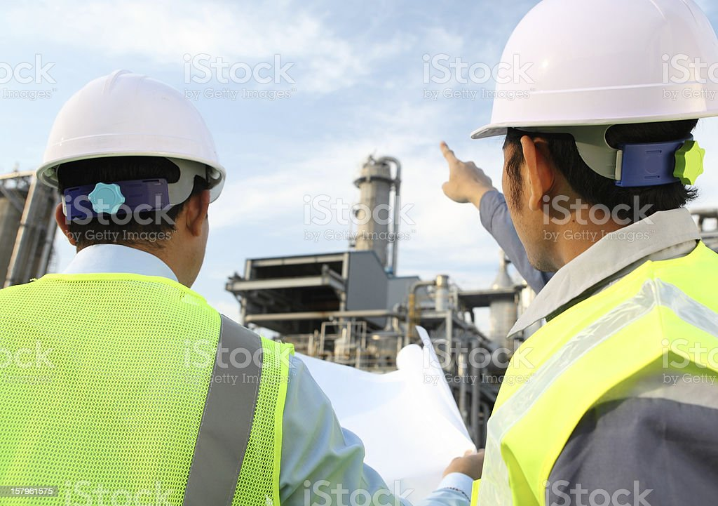 Two engineers discussing a new project and looking at plans royalty-free stock photo