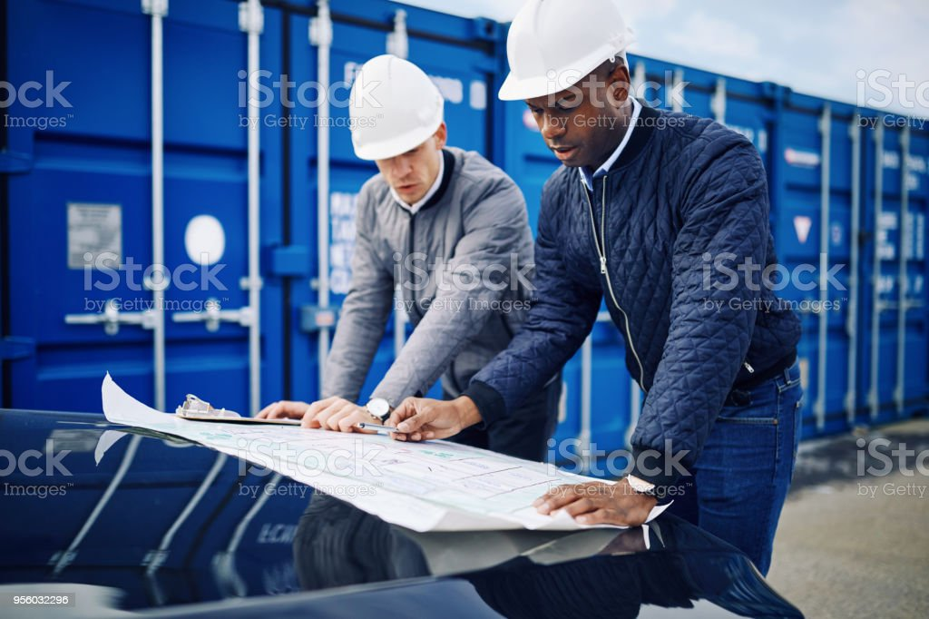 Two engineers leaning on the hood of a truck discussing building...