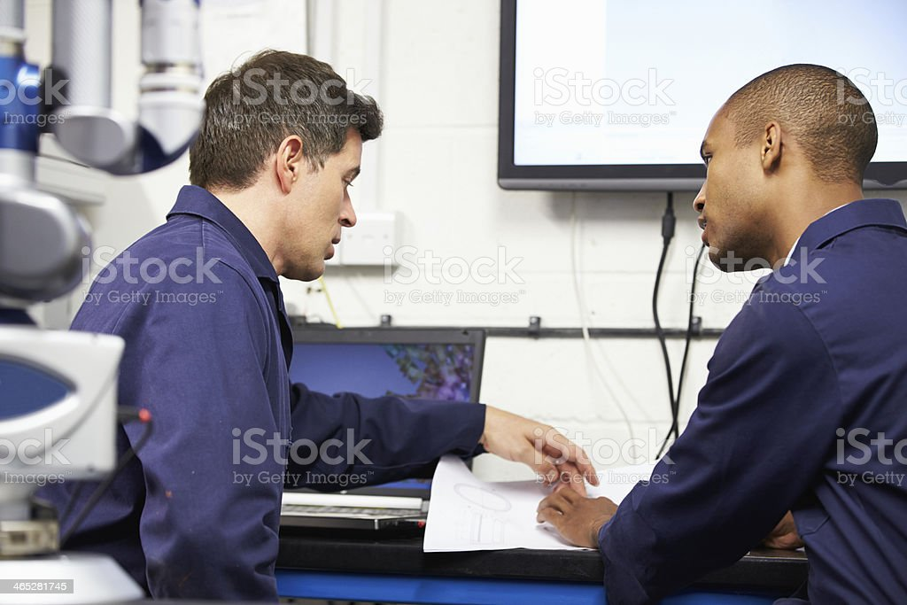 Two Engineers Discussing Plans With CMM Arm In Foreground stock photo