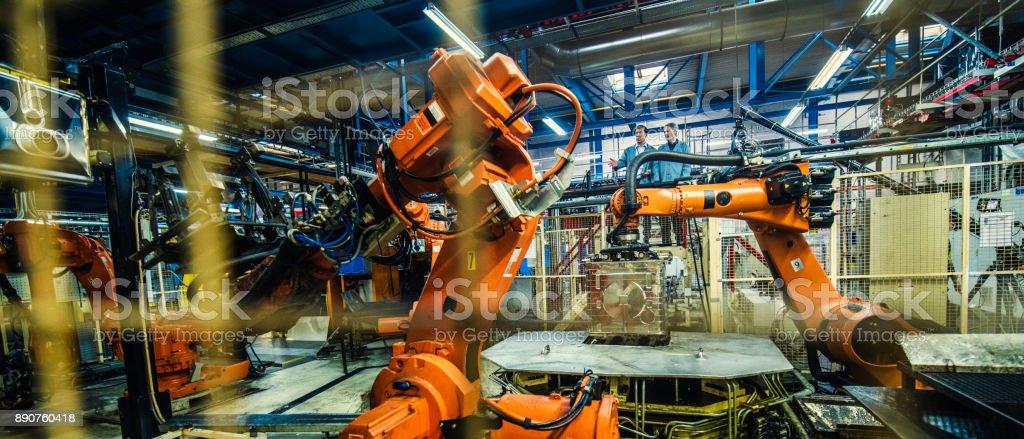 Zwei Ingenieure untersuchen Atuomated Roboterarme – Foto