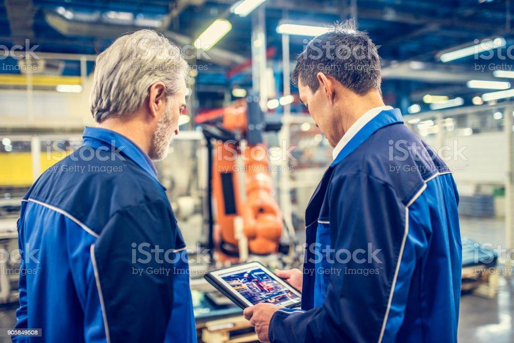 Zwei Ingenieure untersuchen Roboterarm in Fabrik – Foto