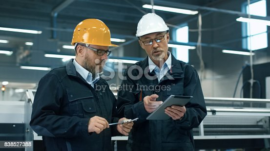 istock Two engineers in hardhats discuss information on a tablet computer while standing in a factory. 838527388
