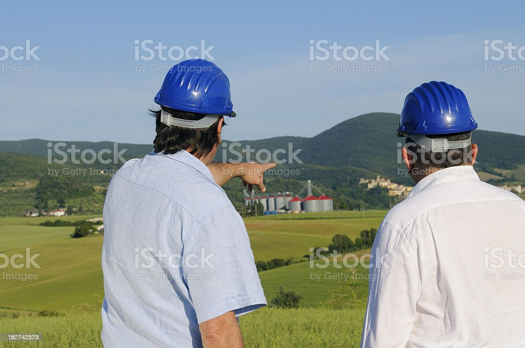 Two engineers or geologists in the countryside.Silos in the background