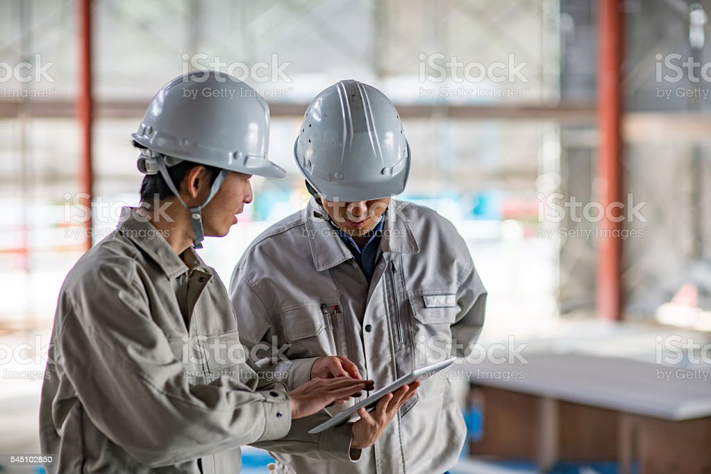 Two engineers looking at a digital tablet at building site stock photo