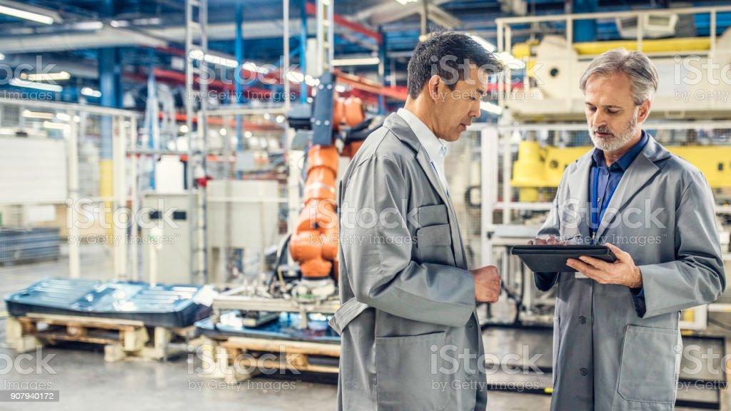 Zwei Ingenieure Blick auf digital-Tablette in der Nähe von der Produktionslinie – Foto