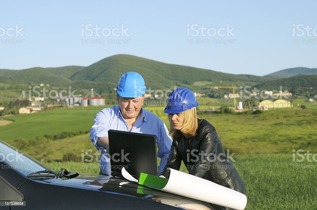 Two Engineers Planning PC in a Green Field royalty-free stock photo