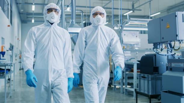 Two Engineers/ Scientists in Hazmat Sterile Suits Walking Through Technologically Advanced Factory/ Laboratory. Clean High-Tech Environment with CNC Machinery. stock photo