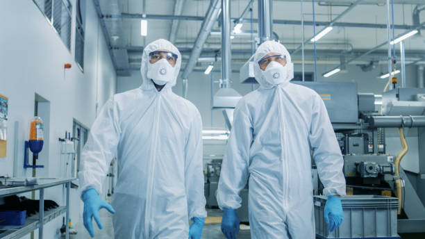 Two Engineers/ Scientists in Hazmat Sterile Suits Walking Through Technologically Advanced Factory/ Laboratory. Clean High-Tech Environment with CNC Machinery. Two Engineers/ Scientists in Hazmat Sterile Suits Walking Through Technologically Advanced Factory/ Laboratory. Clean High-Tech Environment with CNC Machinery. cleanroom stock pictures, royalty-free photos & images