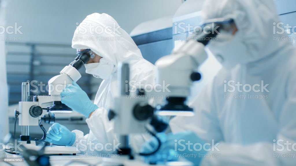 Two Engineers/ Scientists/ Technicians in Sterile Cleanroom Suits  Control Manufacturing Machinery Work and Use Microscopes for Component Adjustment and Research. They Work in an Electronic Components Manufacturing Factory. stock photo