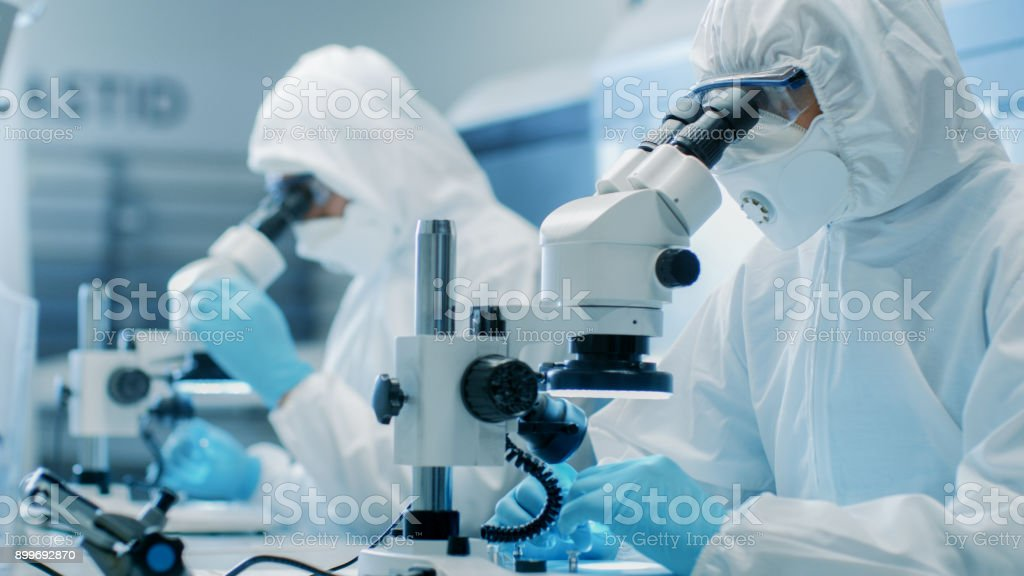 Two Engineers/ Scientists/ Technicians in Sterile Cleanroom Suits Use Microscopes for Component Adjustment and Research. They Work in an Electronic Components Manufacturing Factory. stock photo