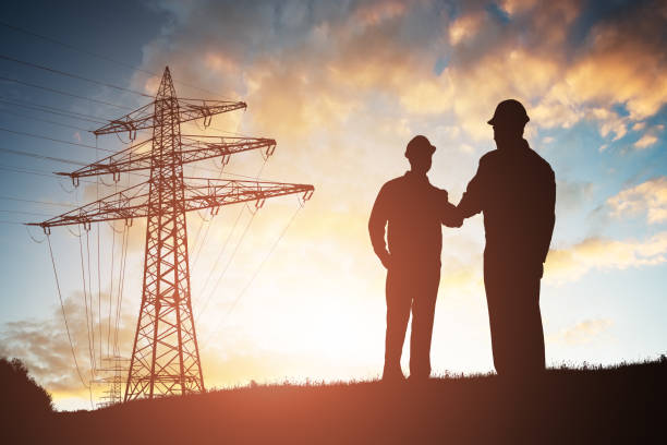 two engineers shaking hands against dramatic sky - rete elettrica foto e immagini stock