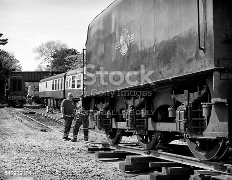 Sheringham, Norfolk, England - May 5, 2016: Two engineers overseeing the tricky process of transferring a steam engine's coal tender from the back of a flatbed lorry to the existing railway track, where it will be collected by a diesel shunting engine. The steam engine is number 45337 of the LMS Stanier Class) being delivered to Sheringham station from where the North Norfolk Railway - a heritage line - operates. Sheringham is a coastal town in Norfolk, eastern England, and the line runs on former M&GN Railway tracks between Sheringham and Holt. The North Norfolk Railway operates a variety of engines and carriages, both steam and diesel. The photograph was taken in the public car park behind the station.