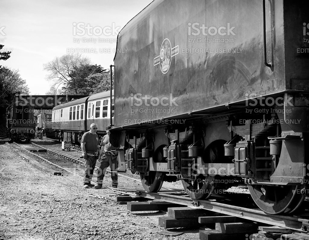 Two engineers unloading a tender to the rails stock photo
