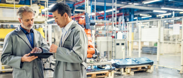 two engineers using digital tablet in a factory - robotics manufacturing stock photos and pictures