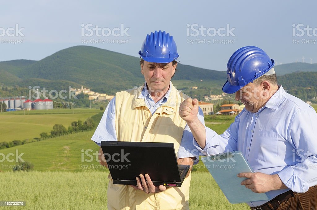 Two Engineers with PC Discussing in the Countryside royalty-free stock photo