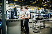 Two printing factory engineers working at a console together.