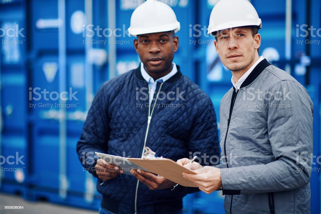 Two engineers tracking inventory using a clipboard and digital tablet...