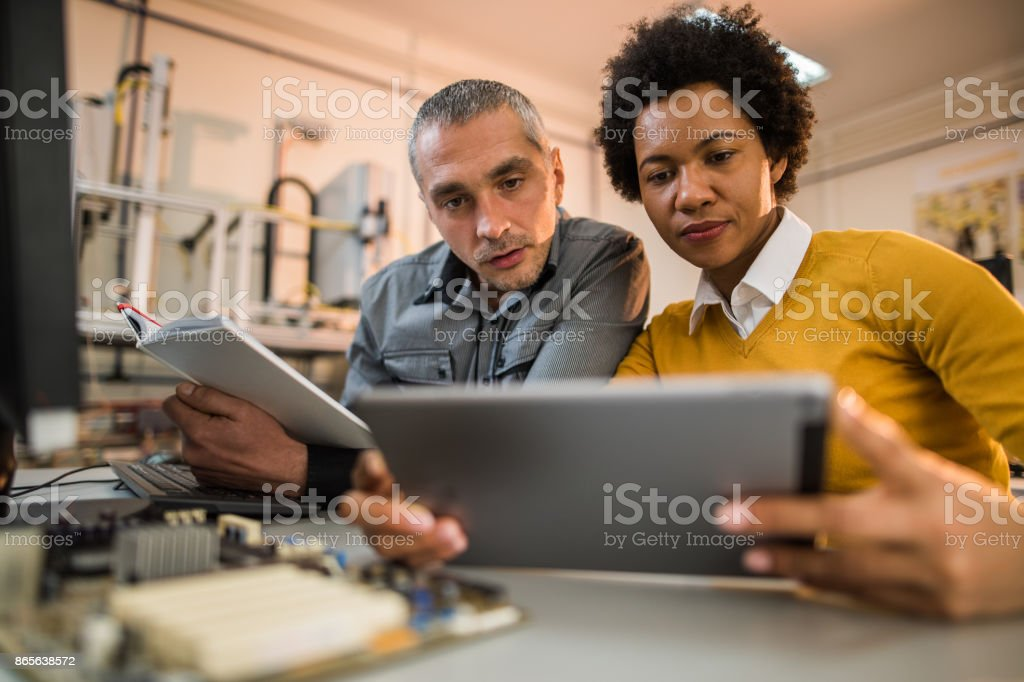 Two engineers working on digital tablet in tech laboratory. stock photo