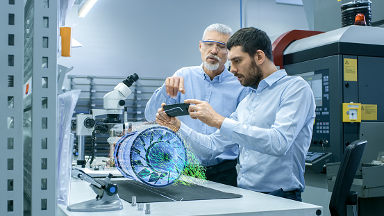 istock Two Engineers Works with Mobile Phone Using Augmented Reality Holographic Projection 3D Model of the Engine Turbine Prototype. Development of Virtual Mixed Reality Application. 938057536