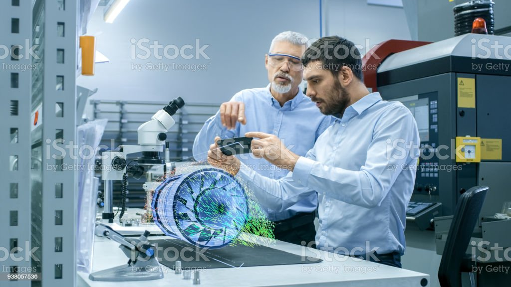 Two Engineers Works with Mobile Phone Using Augmented Reality Holographic Projection 3D Model of the Engine Turbine Prototype. Development of Virtual Mixed Reality Application. stock photo
