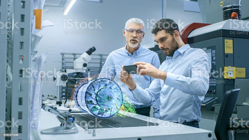 Zwei Ingenieure arbeiten mit Mobiltelefon Augmented Realität holographische Projektion 3D Modell des Prototyps Engine Turbine. Entwicklung der virtuellen Mixed-Reality-Anwendung. – Foto