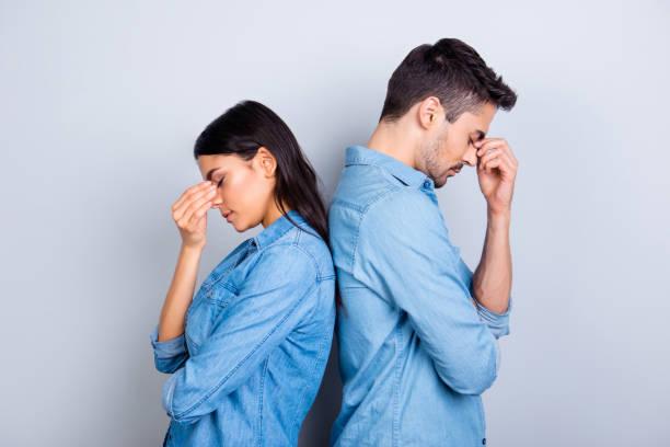 i̇ki girişimciler overworked holding onların parmak burun gözler, genç aile ilişkisi arasındaki gri arka plan üzerinde duran çıkmaz geldi - samimi olma stok fotoğraflar ve resimler