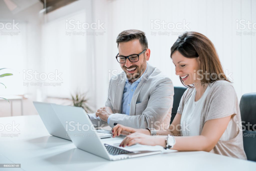 Two entrepreneurs sitting together working in an office stock photo