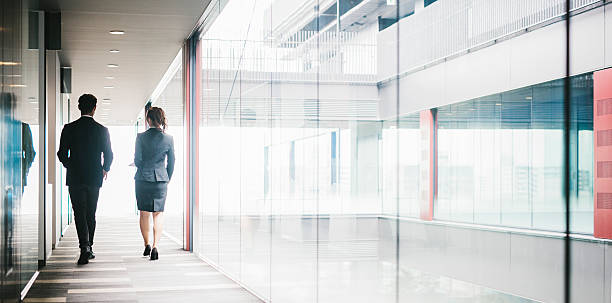 two entrepreneurs walking down the hallway - ビジネスフォーマル ストックフォトと画像