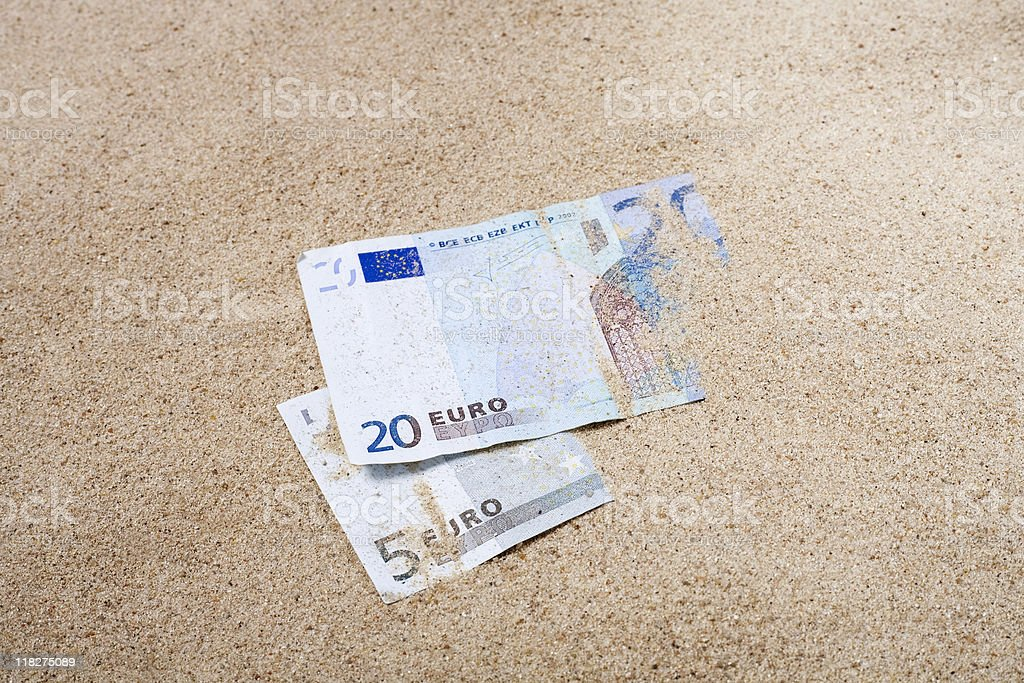 Two Euro banknotes half buried in the sand royalty-free stock photo