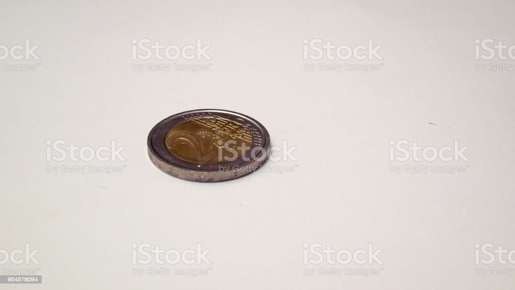 two euro coin turns on itself until it stops stock photo