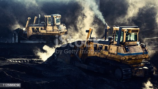 508140747 istock photo Two excavators are working, coal mining, sunlight 1125889290