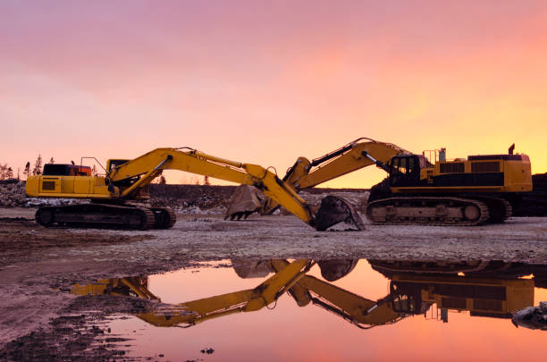 Two excavators on a construction site at sunset stock photo