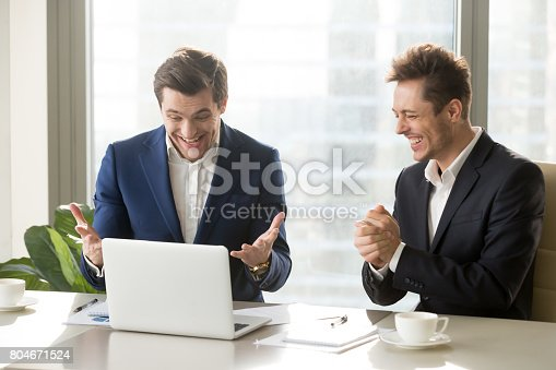 istock Two excited businessmen celebrating victory, funny positive emotions at workplace 804671524